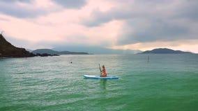 Damen i bikini simmar sammanträde på paddleboard för att sätta på land lager videofilmer