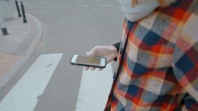 Damen korsar vägen och använder navigeringen App på hennes Smartphone arkivfilmer