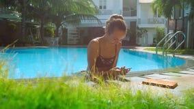 Damen med kroppen i pölvatten överför sms på telefonen på barriären lager videofilmer