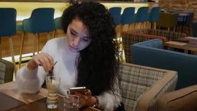 Damen med lockigt hår i en restaurang arbetar på telefonen och dricker kaffe stock video