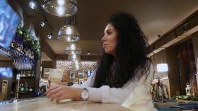 Damen med lockigt hår i en restaurang dricker kaffelatte och leende arkivfilmer