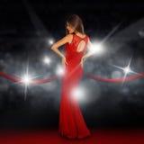 Damen på röd matta poserar i paparazziexponeringar royaltyfri fotografi