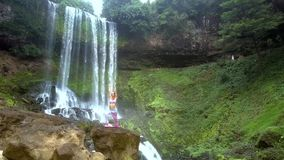Damen rymmer yoga poserar med händer ovanför huvudet vid vattenfallet stock video