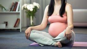 Damen som gör yoga för den tonade gravida fående kroppen, meditationen och kopplar av tillvägagångssätt arkivfoton