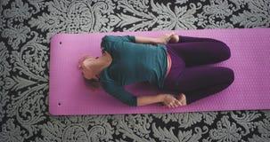 Damen som sträcker kroppen, gör yogaövningar i morgonen hemma henne som sitter i den rosa matta sunda livsstilen stock video
