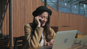 Damen talar vid mobiltelefonen och skriver på bärbara datorn i öppen terrass för kafé arkivfilmer