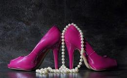 Damen zacken hohe Absätze mit langem Strang von weißen Birnen gegen a aus Lizenzfreie Stockfotos
