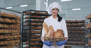 Damenbäcker mit einem schönen Lächeln, das einen Korb mit frischem gebackenem Brot hält und gerade zur Kamera in einer Bäckerei s stock footage