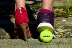 Damenbeine, ein Fuß im Gerichtsschuh und der andere Fuß in einem Sportschuh und in einem Tennisball mit der Aufschrift 2020 Stockfotografie