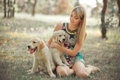 Damenfrau der reizenden Szene des Retrieverwelpen genießen schöne blonde, Sommerzeitferien mit Elfenbeinweiß Labrador aufzuwerfen Lizenzfreie Stockfotografie