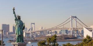 Damenfreiheit gegeneinander gehalten gegen Regenbogen-Brücke in Tokyo, Japan Stockfotografie