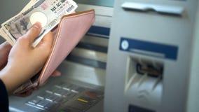 Damenhände, die japanische Yen in Geldbörse, Bargeld zurückgenommen von ATM, reisend einsetzen lizenzfreie stockfotografie