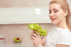 Damenlächeln beim Betrachten des Salats Stockbild