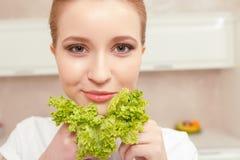Damenlächeln beim Halten des Kopfsalates Stockfotografie