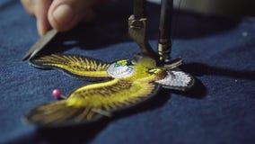 Damenschneider schnitt einen Faden vom Adlersymbol auf Jeans stock footage