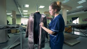 Damenschneiderin bürstet einen Pelzmantel, der an einem Mannequin hängt stock video footage