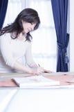 Damenschneiderin, die ein Muster zeichnet stockfotografie