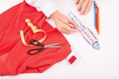 Damenschneiderin, die eine Ausstattungsskizze zeichnet stockbild