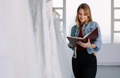 Damenschneiderin, die im Brautbekleidungsgeschäft arbeitet lizenzfreie stockfotos