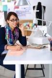 Damenschneiderin, die Kleidungsmuster auf Papier entwirft stockfotografie