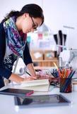 Damenschneiderin, die Kleidungsmuster auf Papier entwirft lizenzfreie stockfotografie