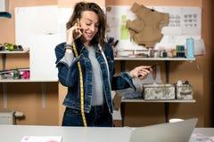 Damenschneiderin, die am Telefon im Arbeitsraum spricht stockfoto