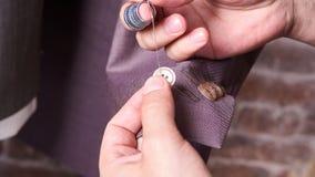 Damenschneiderin näht einen Knopf auf Jacke Stockfotos