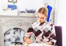 Damenschneiderin zeichnet eine Figurine lizenzfreie stockbilder