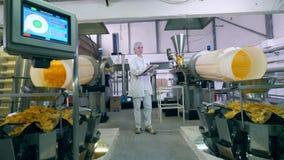 Damentechniker kontrolliert die Ausrüstung, die Kartoffelchips freigibt stock video