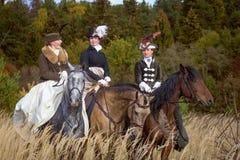 Damer i 19th hästar för århundradeklänningridning Royaltyfria Bilder