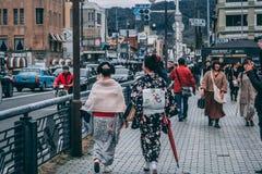 Damer i traditionella japanska dräkter som går de Kyoto gatorna arkivbilder