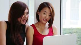 Damer med bärbara datorn lager videofilmer