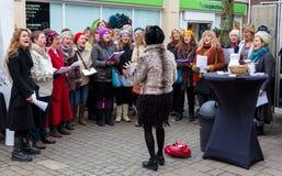 Damer sjunga i kör att sjunga i Frome arkivfoton