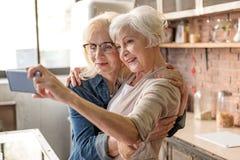 Dames âgées gaies faisant le selfie dans la cuisine Photo libre de droits
