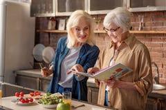 Dames âgées gaies lisant dans la cuisine Images libres de droits