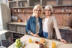 Dames âgées heureuses embrassant dans la chambre de cuisinier Photo stock