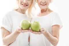 Dames âgées heureuses montrant des fruits frais Photographie stock libre de droits