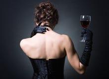 dames avec une glace de vin rouge. Image stock