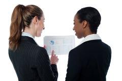 Dames d'affaires examinant des documents Photographie stock