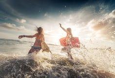 Dames de surfer à la mer Photographie stock libre de droits