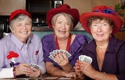 Dames die rode hoedenspeelkaarten dragen Stock Afbeelding