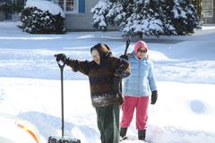 Dames die Sneeuw scheppen stock foto