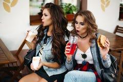 Dames en limonade de café et hamburgers potables de consommation Photos stock