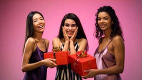 Dames het gifting stelt aan vriend voor, die verjaardagspartij in pyjama's vieren, pret stock foto