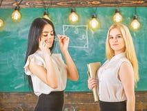 Dames klaar om priv?-les, bord op achtergrond te beginnen Aantrekkelijke leraren die zich na klassen overwerken leraren royalty-vrije stock afbeeldingen