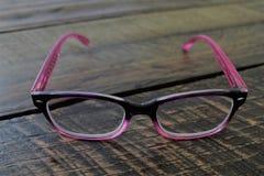 Dames roses élégantes lisant des lunettes Images stock
