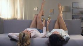 dames se trouvant sur le sofa avec soulever des jambes et boire du champagne, refroidissant banque de vidéos