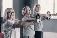 Dames supérieures effectuant la séance d'entraînement de disque de poids Photos stock