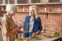 Dames supérieures parlant dans la chambre de cuisinier Photographie stock