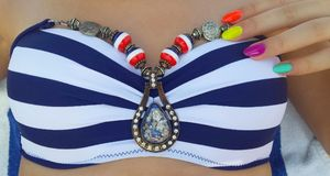 Dames utilisant des accessoires de médaillon sur le maillot de bain d'été images libres de droits